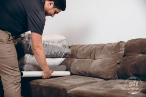 sewage backup cleanup technician packing out furniture